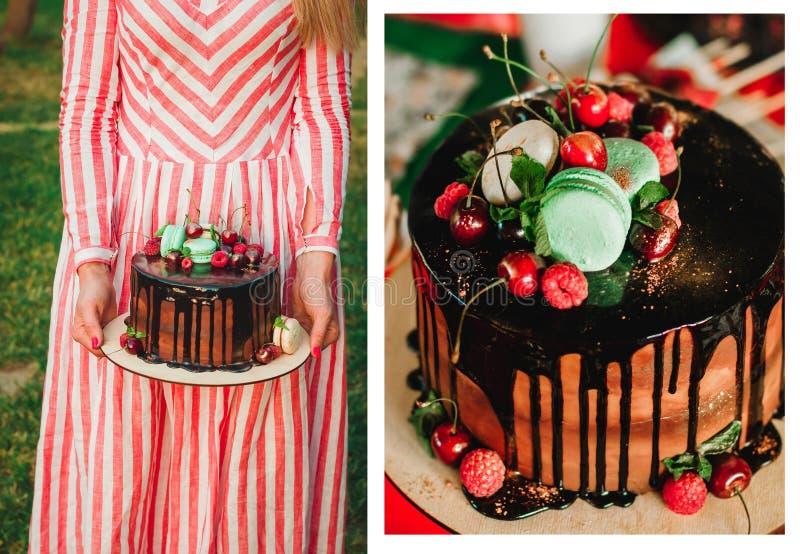 Dolce di cioccolato con i macarons, le ciliege ed i lamponi in mani di una donna in un vestito a strisce Bello dessert fotografie stock