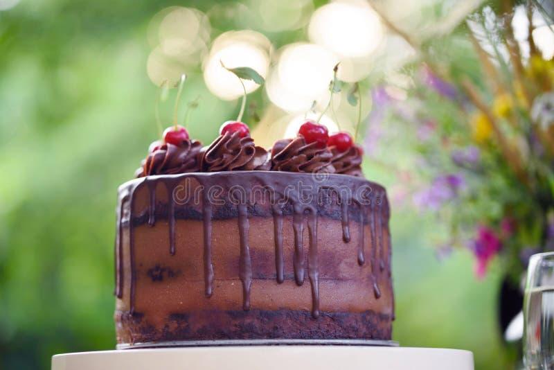 Dolce di cioccolato con la ciliegia su un bello fondo del bokeh fotografia stock