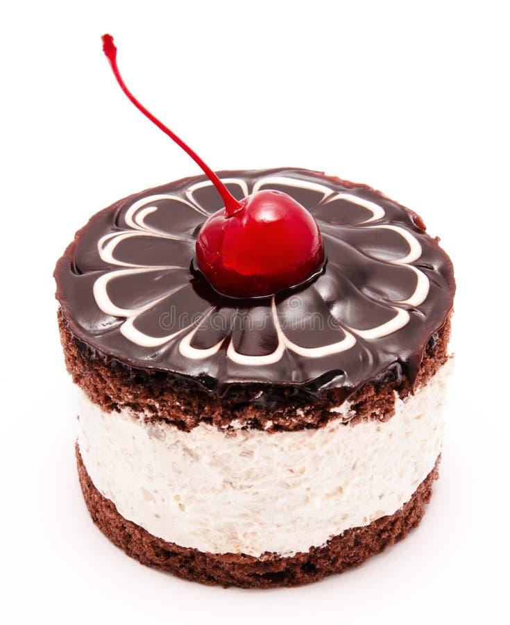 Dolce di cioccolato con la ciliegia sulla glassa superiore isolata fotografia stock libera da diritti