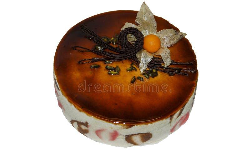 Dolce di cioccolato coperto di salsa del caramello e decorato con il fiore del physalis immagini stock libere da diritti