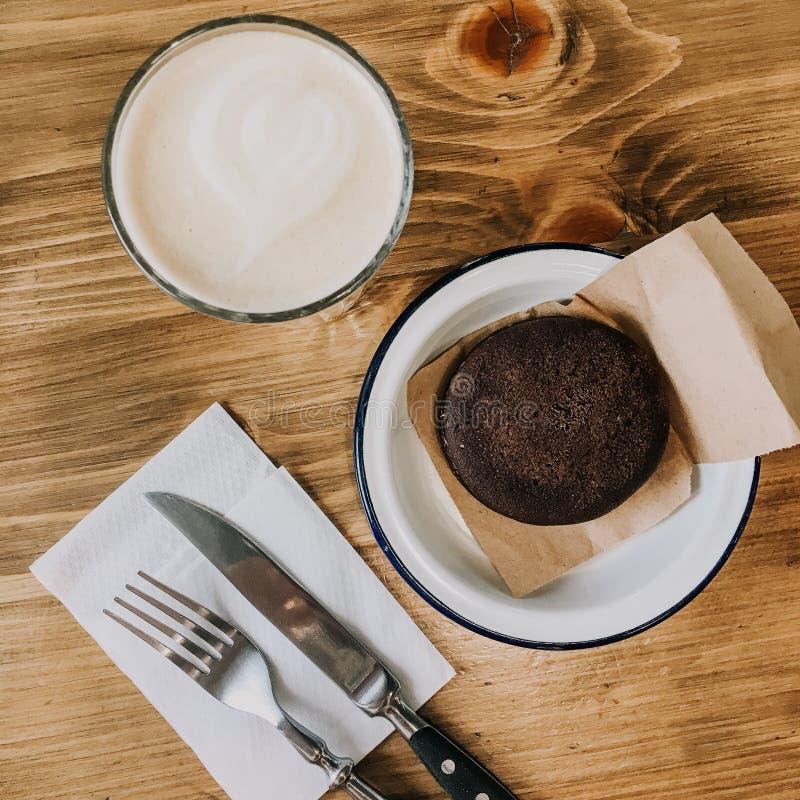 Dolce di cioccolato e della tazza di caff? sulla tavola di legno Forcella d'annata e coltello Piatto d'annata della foto di Squre immagine stock libera da diritti