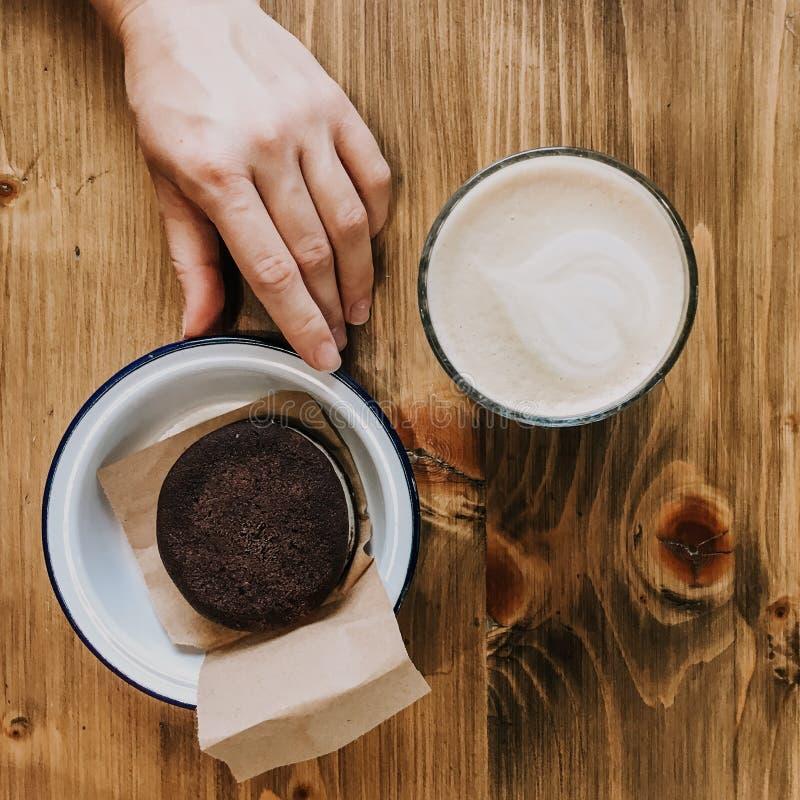 Dolce di cioccolato e della tazza di caff? sulla tavola di legno Mano che tocca un dolce Piatto d'annata della foto di Squred fotografia stock libera da diritti