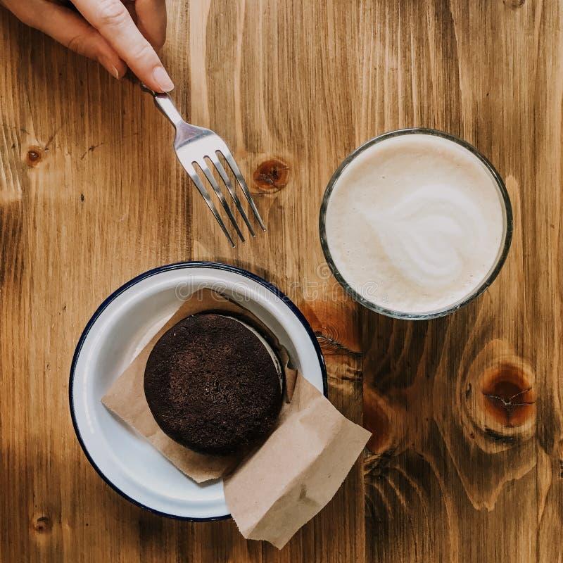 Dolce di cioccolato e della tazza di caff? sulla tavola di legno Mano con una forcella che tocca un dolce Piatto d'annata della f fotografia stock libera da diritti