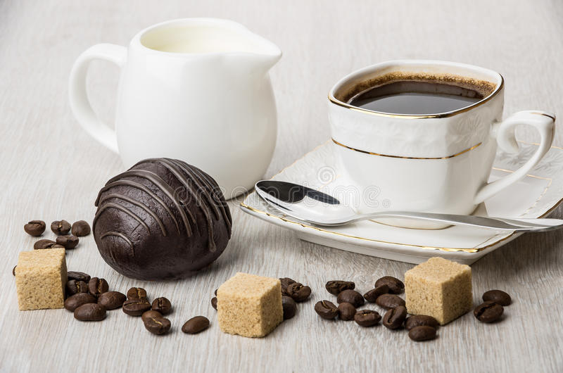 Dolce di cioccolato, latte della brocca, pezzi di zucchero e tazza di caffè immagine stock