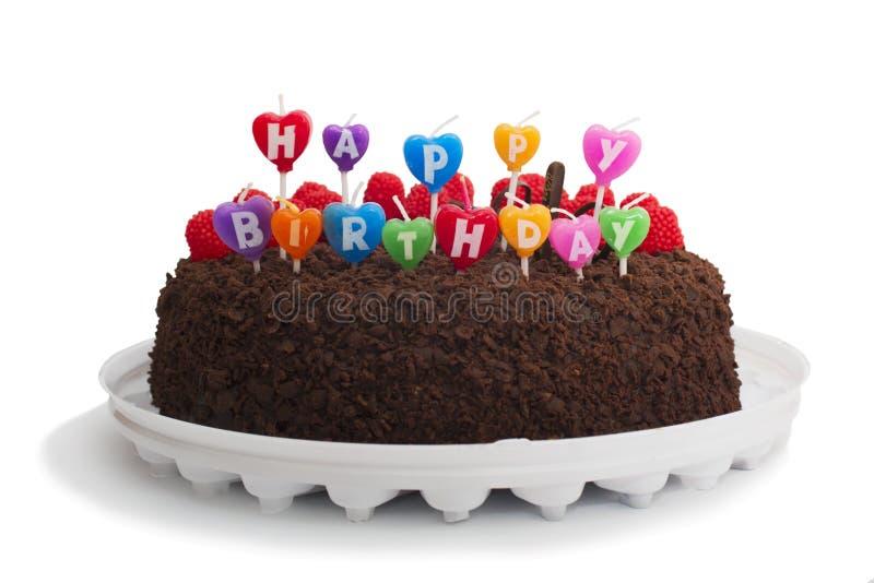 Dolce di cioccolato saporito con le candele di buon compleanno, isolate su fondo bianco immagini stock
