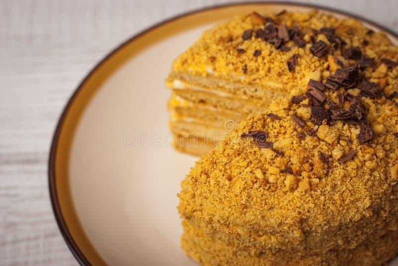Dolce di miele con di pepita di cioccolato sulla fine ceramica del piatto - su fotografie stock