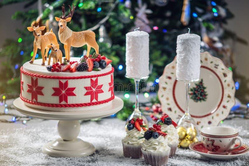 Dolce di natale bianco con l'ornamento rosso su superiore decorato con le figure del mastice dei cervi e delle bacche fresche su  immagini stock