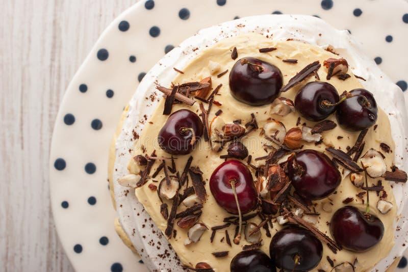 Dolce di Pavlova con freschi di pepita di cioccolato e della ciliegia sulla vista superiore del piatto ceramico immagini stock libere da diritti