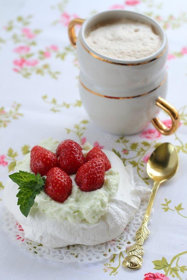 Dolce di Pavlova con le fragole con una tazza di cappuccino su un tovagliolo variopinto fotografia stock