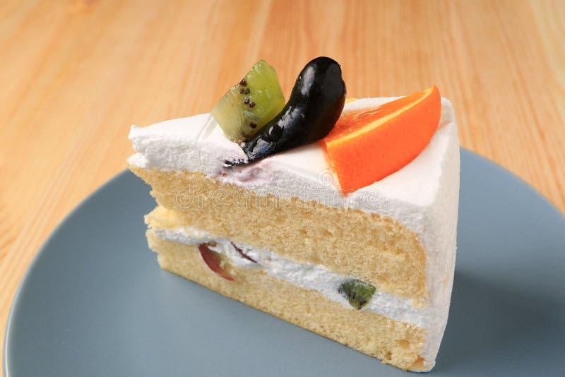 Dolce di strato della spugna della vaniglia completato con i frutti serviti sul piatto blu immagini stock libere da diritti