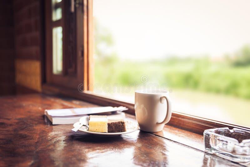 Dolce e tazza di caffè sulla tavola di legno vicino al davanzale della finestra Tempo con il concetto degli spuntini immagini stock