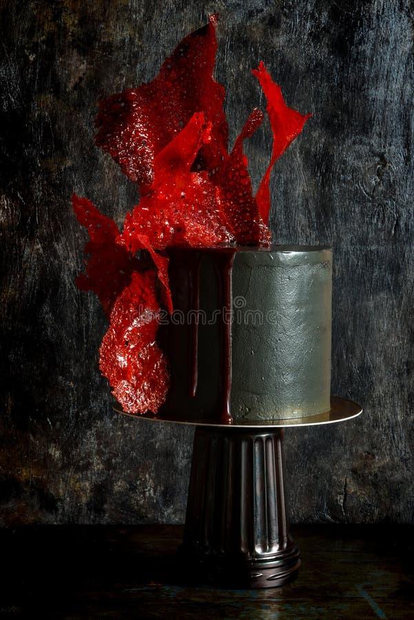 Dolce esagerato di colore nero con la decorazione rossa luminosa del caramello Torta di compleanno affascinante immagine stock