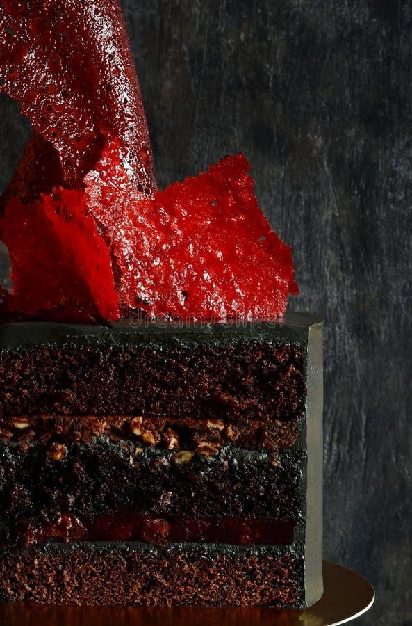 Dolce esagerato di colore nero con la decorazione rossa luminosa del caramello Torta di compleanno affascinante Tagli il primo pi fotografia stock