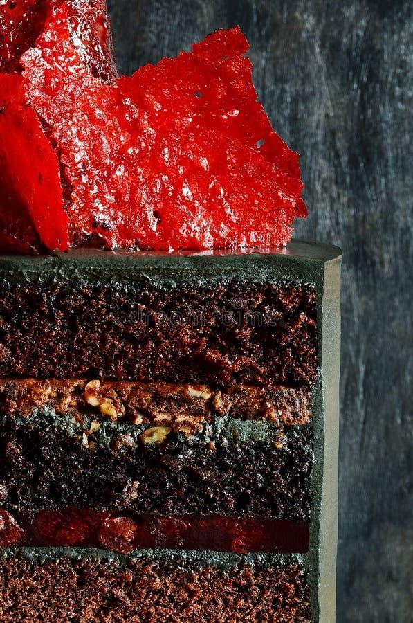 Dolce esagerato di colore nero con la decorazione rossa luminosa del caramello Torta di compleanno affascinante Tagli il primo pi fotografia stock libera da diritti