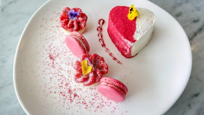 Dolce a forma di della fragola del cuore con i maccheroni rosa - dessert di amore della torta di formaggio immagini stock