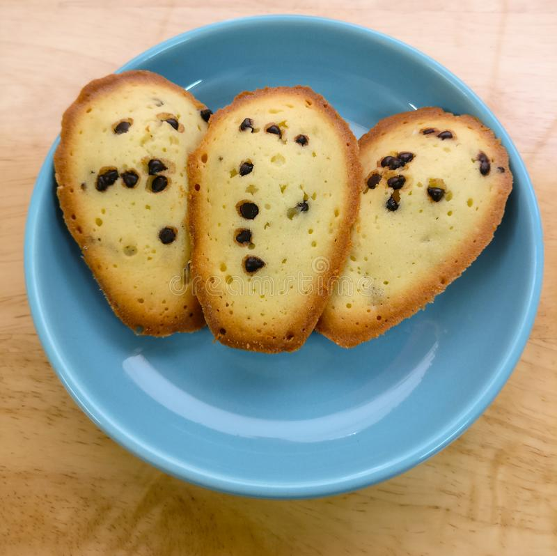 Dolce fresco di Madeleine di pepita di cioccolato su un piatto blu fotografie stock libere da diritti