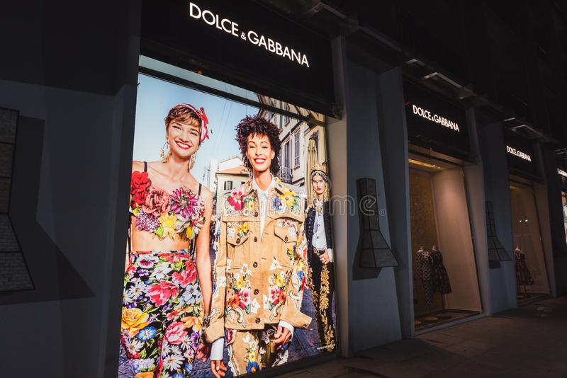 Dolce & Gabbana shop`s exterior at night, front windows with clothes and a poster showing women models and inhabited by alive geck stock images