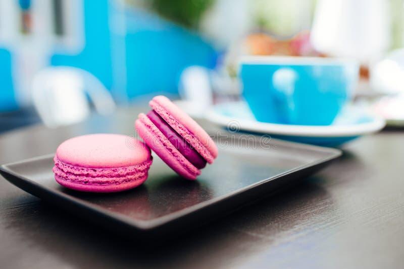 Dolce, macarons freschi con caff? in una tazza blu su una tavola nera fotografie stock