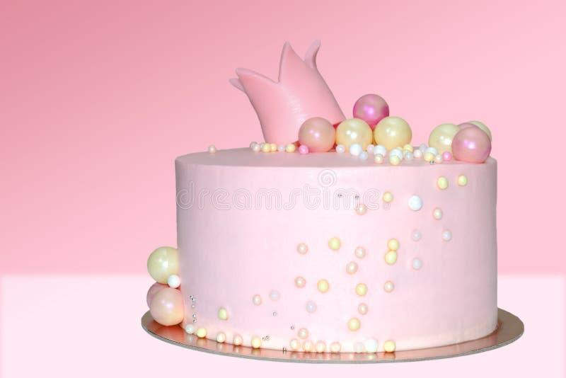 Dolce rosa per una ragazza con una decorazione sotto forma di corona e palle su un fondo isolato fotografie stock