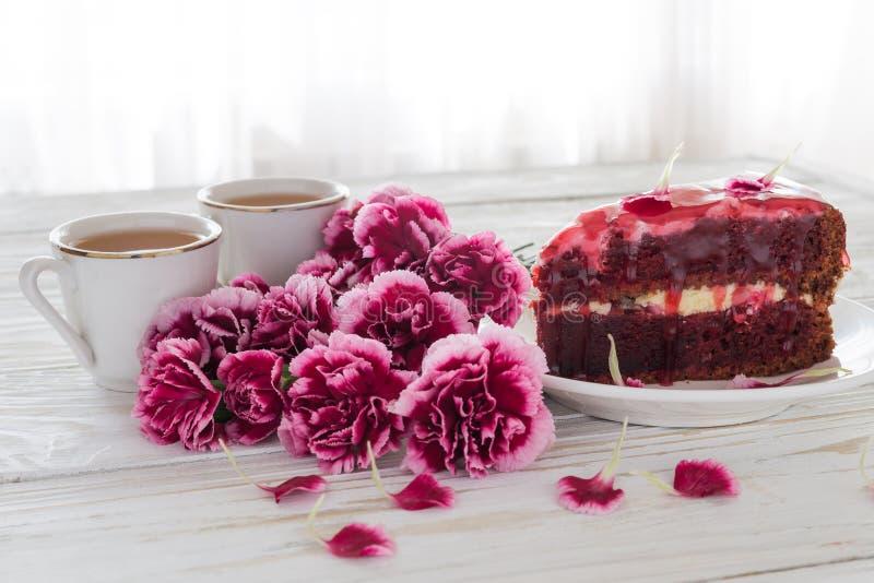 Dolce rosso del velluto, due tazze di tè e garofani rosa fotografia stock
