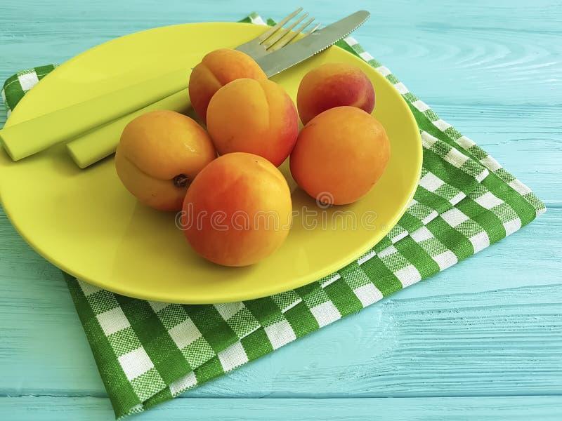 Dolce sano su un piatto di legno blu del coltello del fondo, asciugamano del vegano dell'albicocca fresca immagini stock