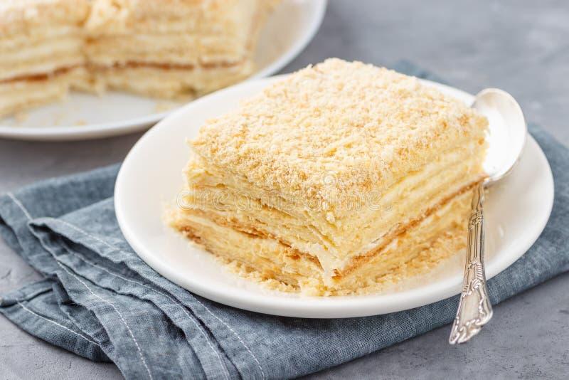 Dolce stratificato con la fetta crema della vaniglia del millefeuille di millefoglie su un piatto bianco fotografia stock