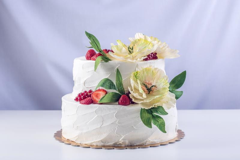 Dolce su due livelli di nozze domestiche decorato con l'uva passa, le fragole ed i fiori gialli Dessert festivo della bacca immagini stock