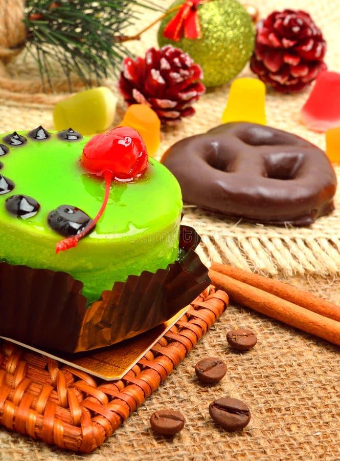 Dolce verde delizioso di Natale con i bastoni o di cannella e della ciliegia immagini stock