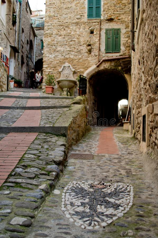 Dolceacqua. A street of the medieval village of Dolceacqua going up the hill with a nobiliar emblem printed on the pavement stock photography