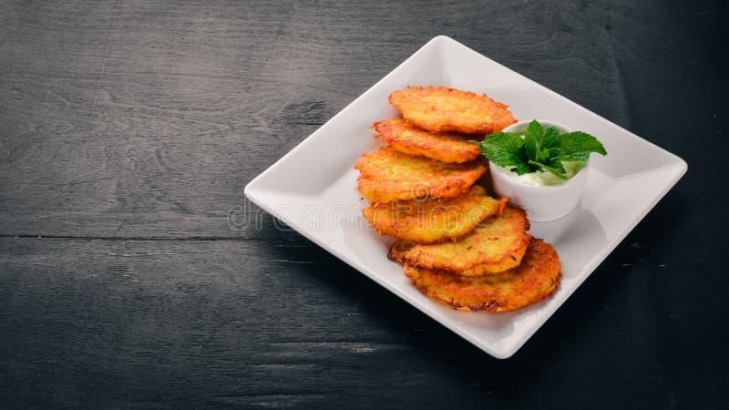 Dolci della patata con panna acida Pancake di patata Cucina ucraina sui vecchi precedenti di legno Spazio libero per testo immagine stock