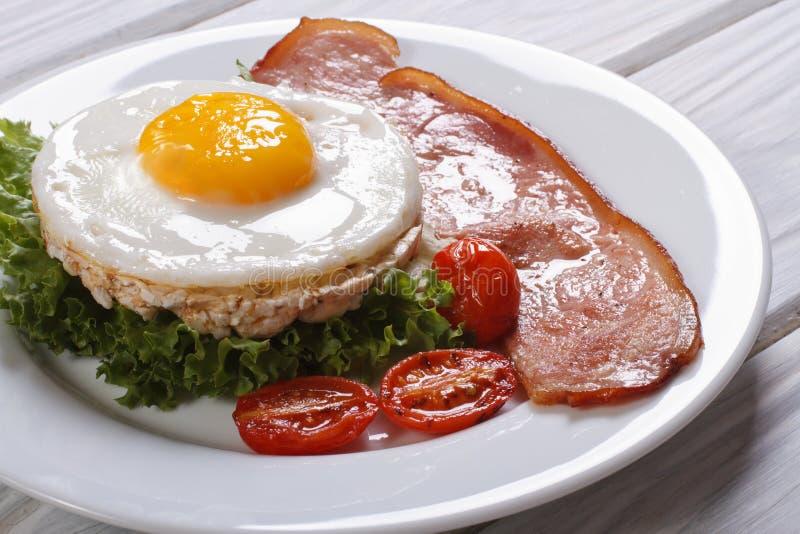 Dolci di riso con le uova, il bacon, la lattuga ed il pomodoro fotografia stock libera da diritti
