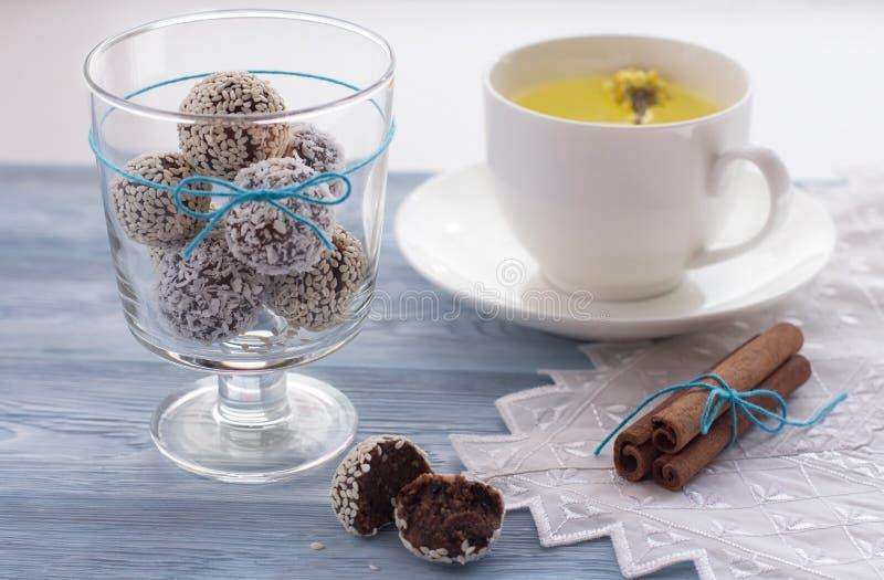 dolci sani casalinghi con i semi di sesamo e la noce di cocco in un vetro, cannella, tisana su un fondo di legno fotografie stock libere da diritti