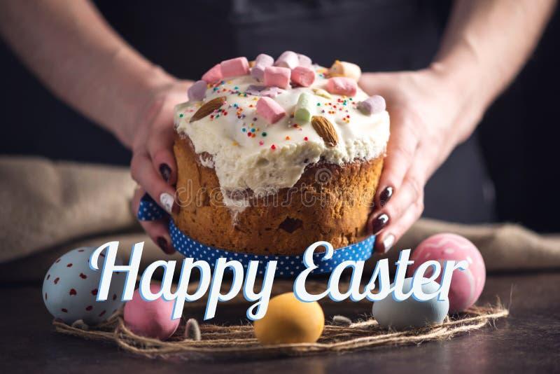 Dolci tradizionali di Pasqua ed uova variopinte e testo su un fondo scuro Scheda di festa immagini stock