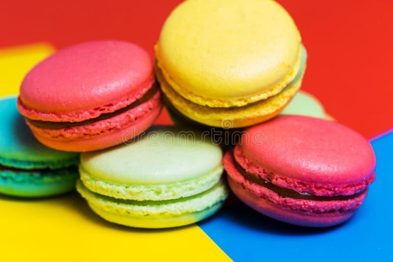 Dolci variopinti dei macarons su un fondo blu, rosa del primo piano, dessert francese verde giallo immagini stock