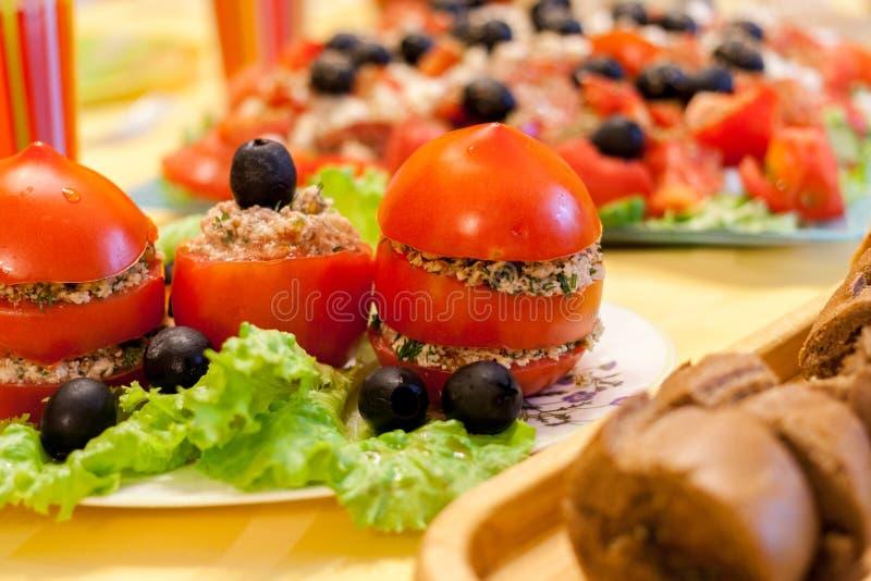Dold tabell med nya röda välfyllda tomater, grönsallat och oliv på vit platta-, bröd- och greksallad royaltyfri fotografi