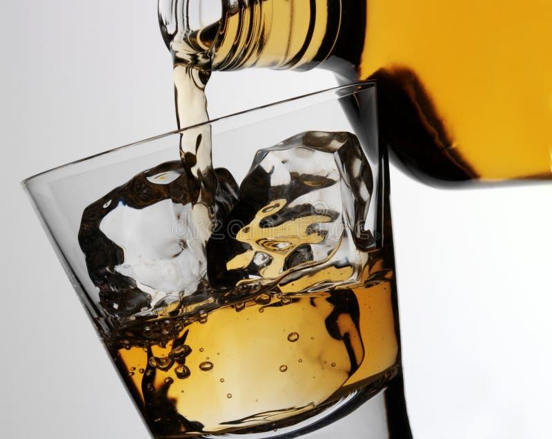 DOLEWANIA szkło bourbonu whisky zdjęcie stock