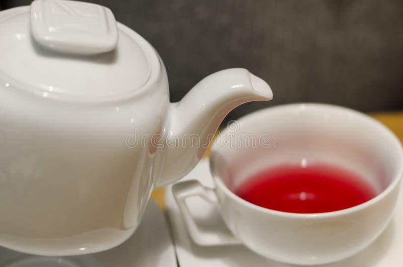 Dolewanie czerwona herbata w filiżankę fotografia stock