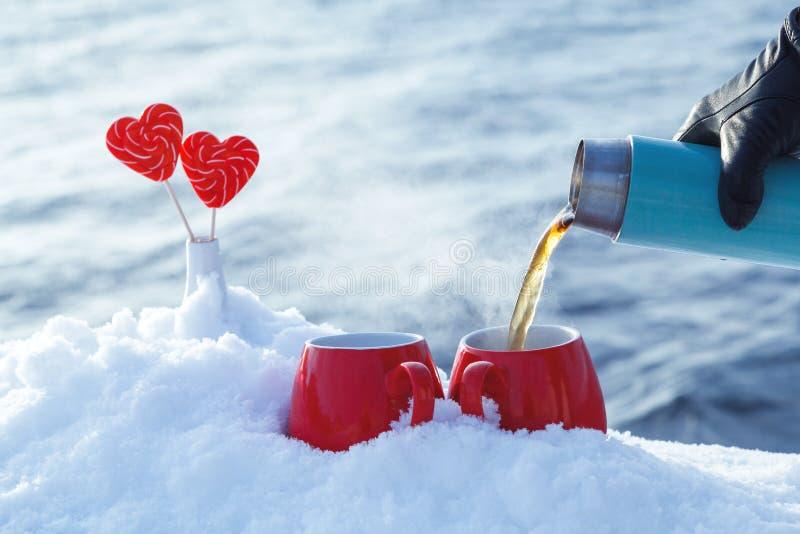 Dolewanie herbata od termosu w pinkinie na walentynka dniu dalej Rewolucjonistka kubki z gorącą herbatą, lizaków serca w śniegu obrazy stock