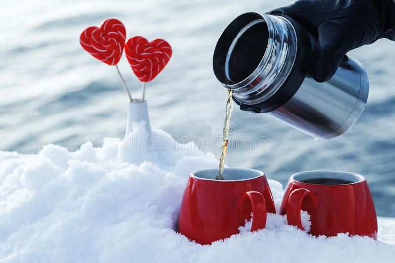 Dolewanie herbata od termosu w pinkinie na walentynka dniu dalej Rewolucjonistka kubki z gorącą herbatą, lizaków serca w śniegu zdjęcie stock