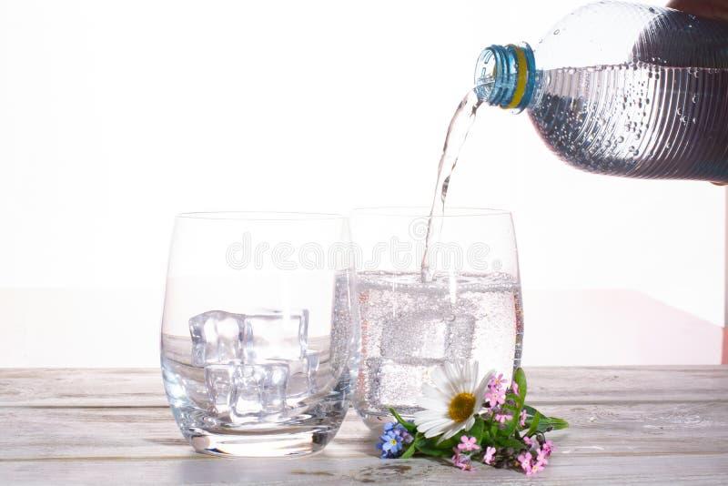 Dolewanie iskrzasta sodowana kopalna napój woda w szkłach z ic fotografia stock