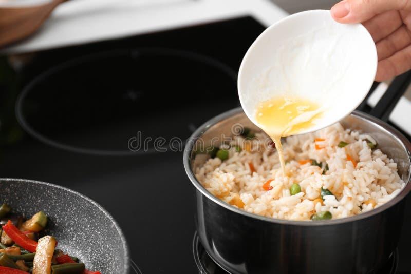 Dolewanie rozciekły masło w rondel z gotowanymi ryż i warzywami w kuchni obraz royalty free