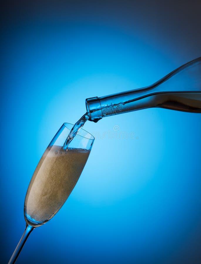Dolewanie szampan od butelki w szkle fotografia stock