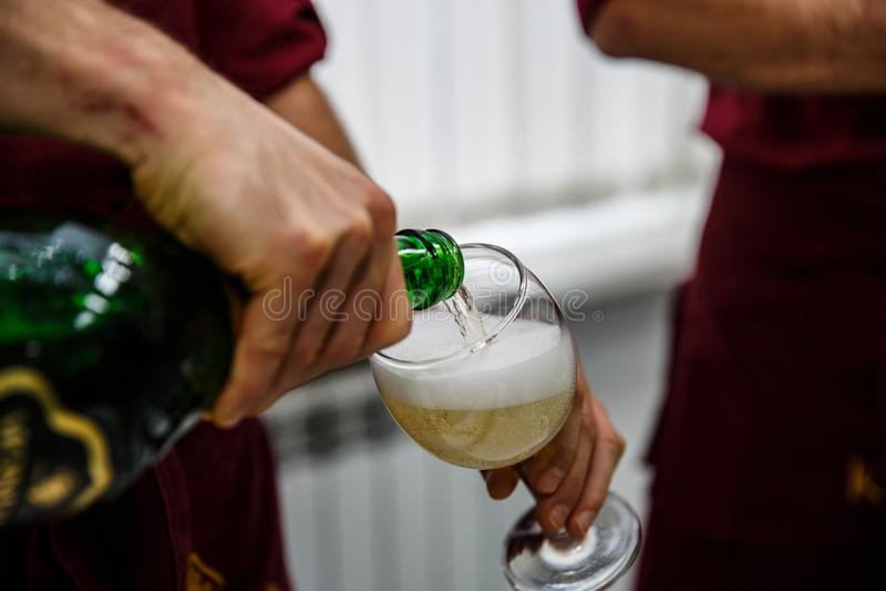 Dolewanie szampan w szkło przy przyjęciem, zamyka up obraz stock