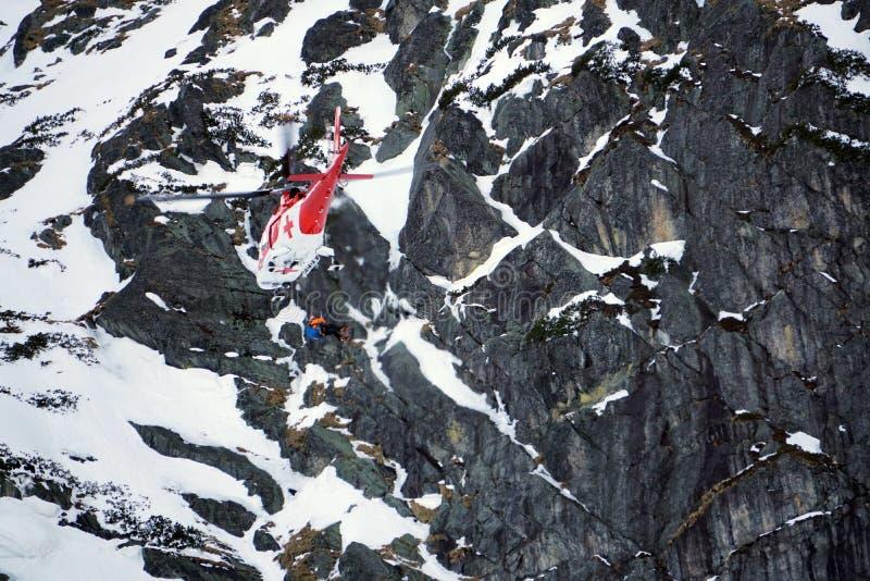 Dolina för Malà ¡ Studenà ¡ - Vysoké Tatry/Slovakien - Februari 15, 2019: Bergräddningsaktionhelikopter i den höga Tatrasen Vyso royaltyfri foto