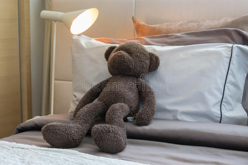 Doll bear and pillows on bed royalty free stock photos