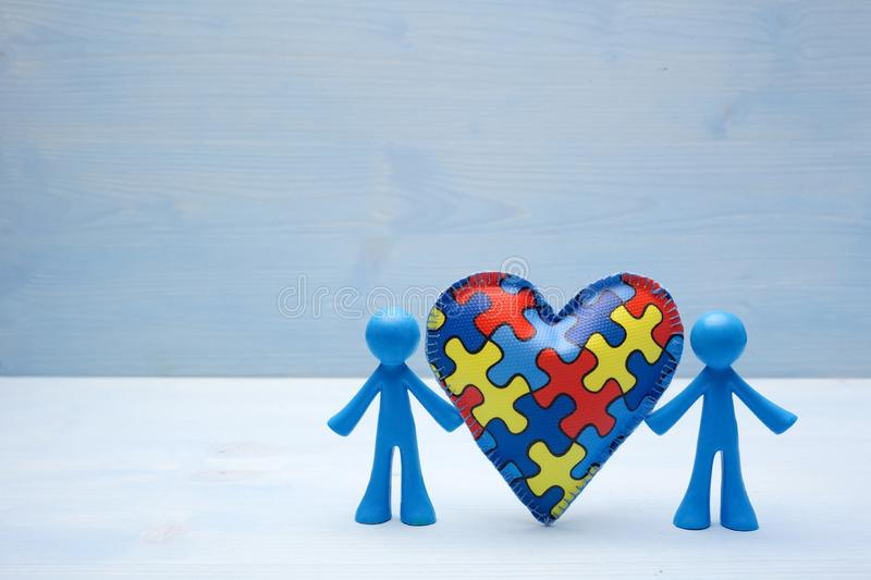Doll children background with symbolic autism puzzle heart stock image