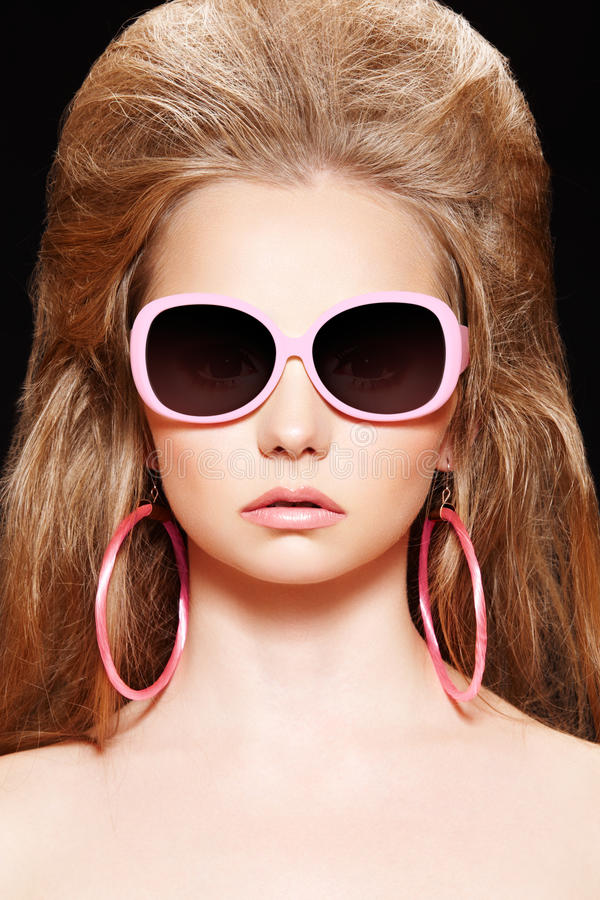 Doll. Fashion model with pink sunglasses, big hair. Close-up portrait of beautiful fashion model with pink doll make-up, plastic sunglasses, circle earrings, big stock photo