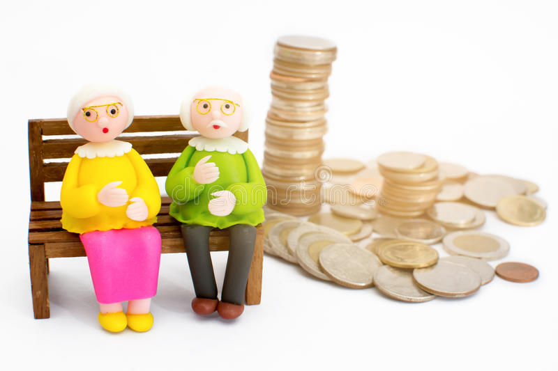 Doll, grandmother. Doll, grandma sitting on a chair next to a pile of money, concept Having money for life is not difficult stock images