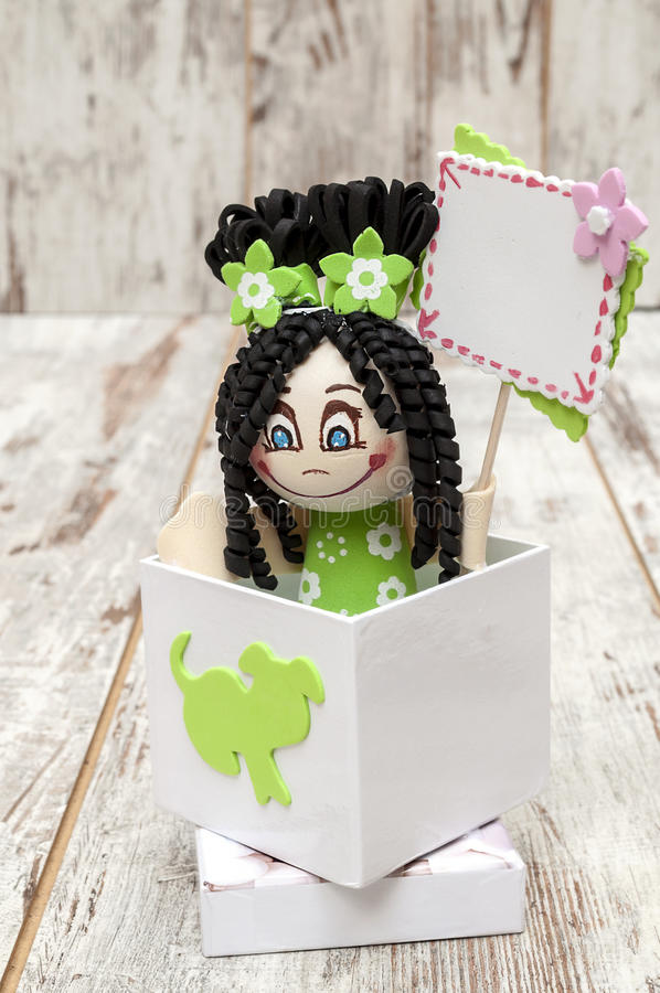 Doll holding a sign. In a box surrounded byrustic backgrouns royalty free stock photo