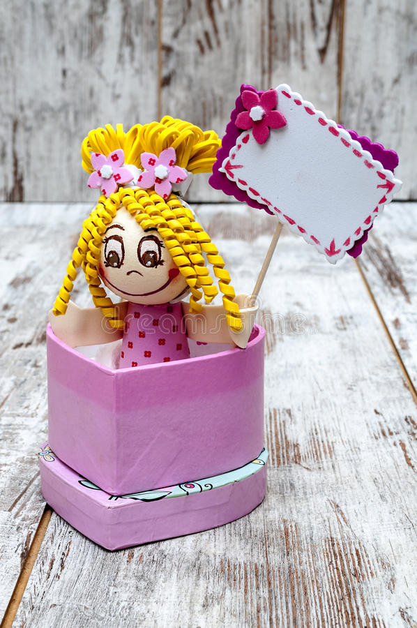 Doll holding a sign. In a heart box surrounded by rustic backgrouns royalty free stock photography